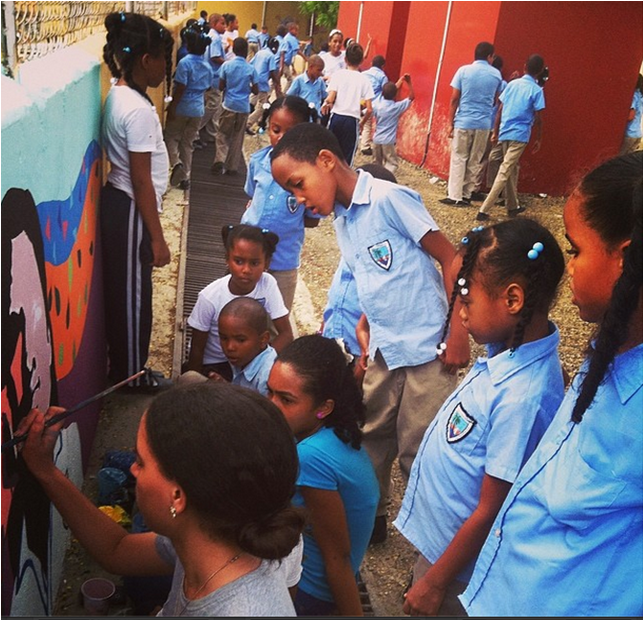 Elementary school students look on while the high school students paint.